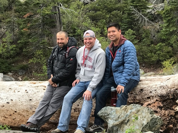 Three guys sitting on a fallen tree