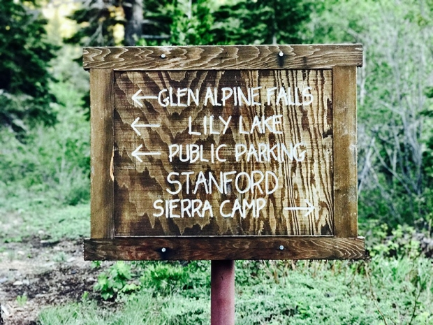 Rustic wooden sign at the camp