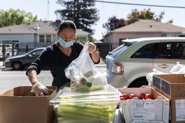 Woman transferring food from food donation box