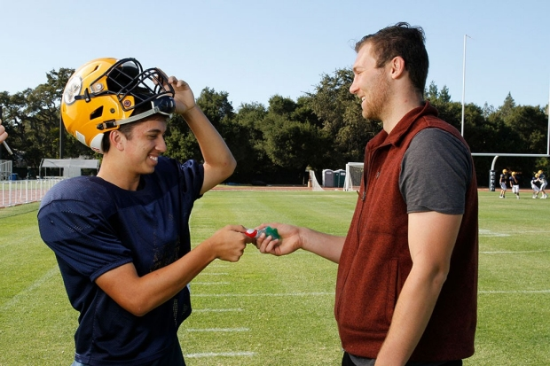 William Mehring hands a mouthguard to a high school football player