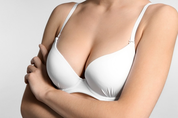 Young woman with beautiful breast on light background, closeup