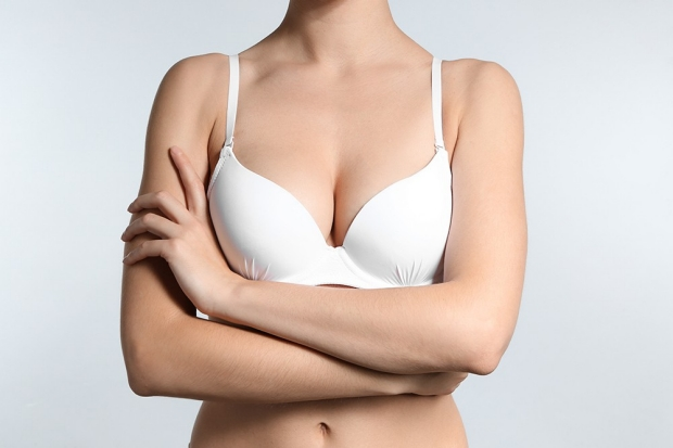 Young woman with beautiful breast on light background
