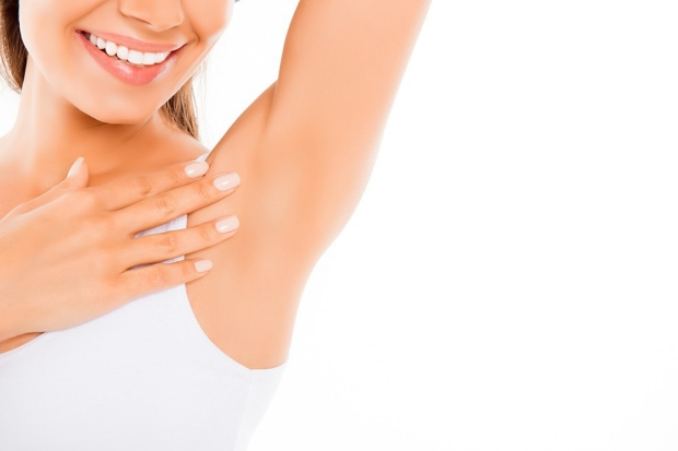 Close up of  happy young woman showing her smooth armpit