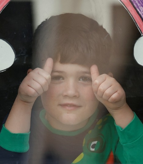 A young boy smiling and giving two thumbs up at the camera with a rainbow drawing taped on the window above him
