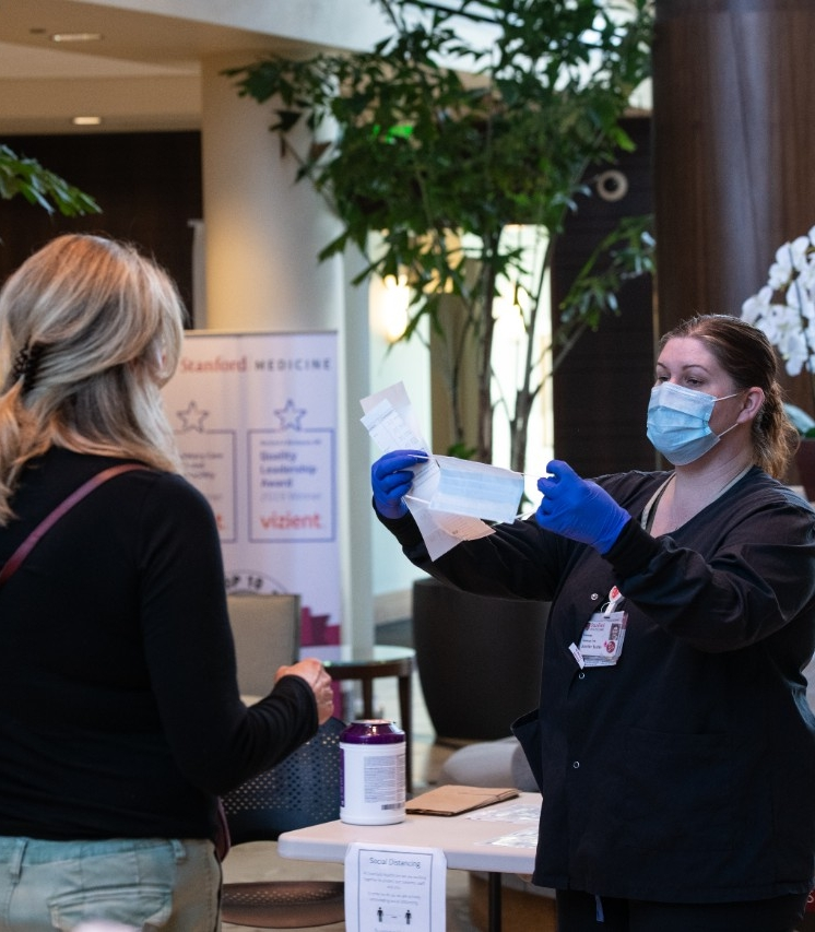 Employee provides mask to patient