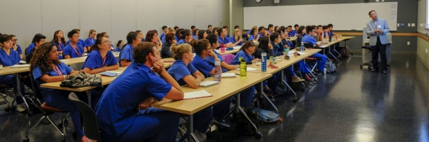 students in blue scrubs watching class presentation