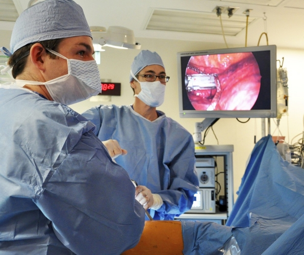 three thoracic surgeons in blue scrubs in operating room