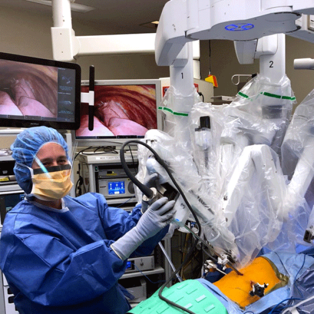 photo of an an assistant at the bedside helping exchange instruments and remove specimens during robotic surgery