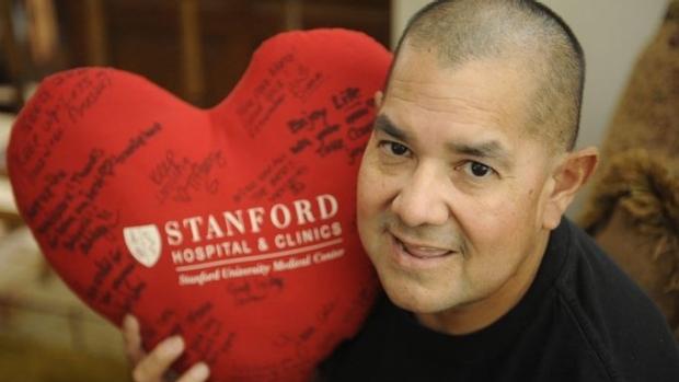 man holding stuffed heart shaped pillow