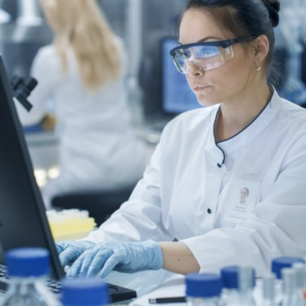 Woman in white coat and blue gloves works at computer, image from HAI Blog post