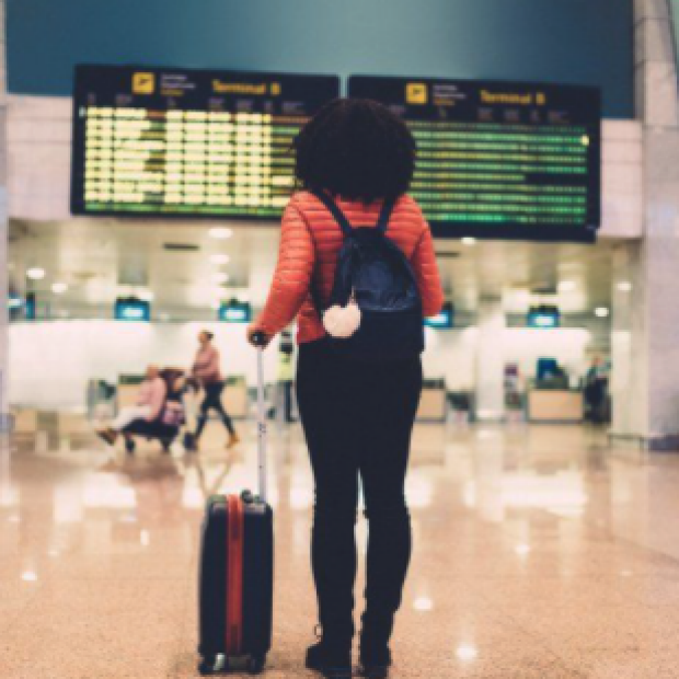 Woman with suitcase stares at arrivals screen at airport, image from UCSF press release
