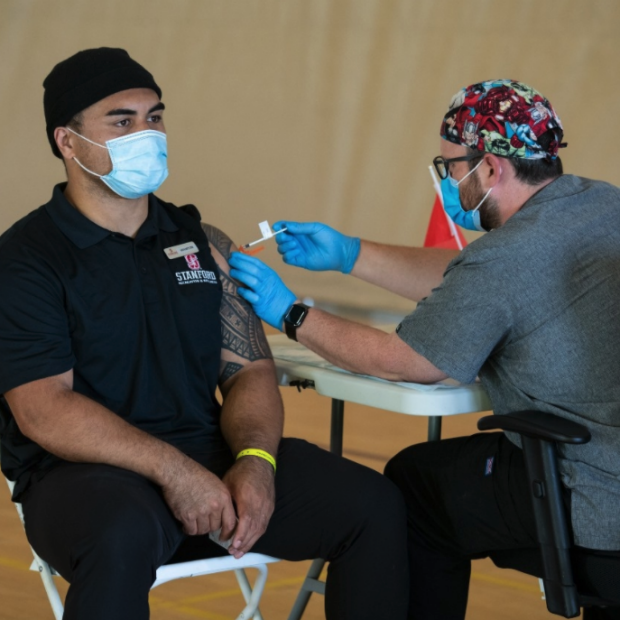 Stanford undergraduate student Houston Heimuli is inoculated with a COVID-19 vaccine. Steve Fisch