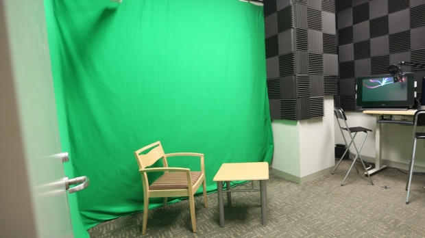 A chair and table are set up in front of a green screen curtain. Off to the right is a computer and walls covered in sound-proofing foam.