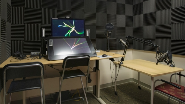 A monitor and a tablet sit on a table with one professional microphone and two chairs. A shorter table on wheels has two professional microphones and a chair. The walls are covered in sound-proofing foam.