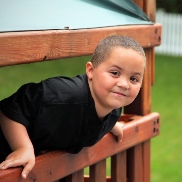 Young boy in black shirt leans over rail and smiles at camera, courtesy of StanfordMed News release