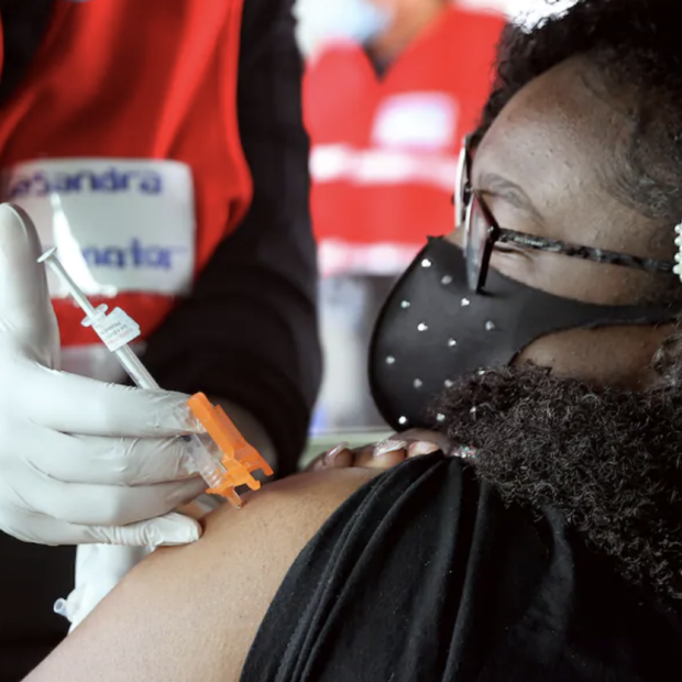 Screenshot of African American woman getting COVID shot from frontline worker, from Washington Post opinion piece