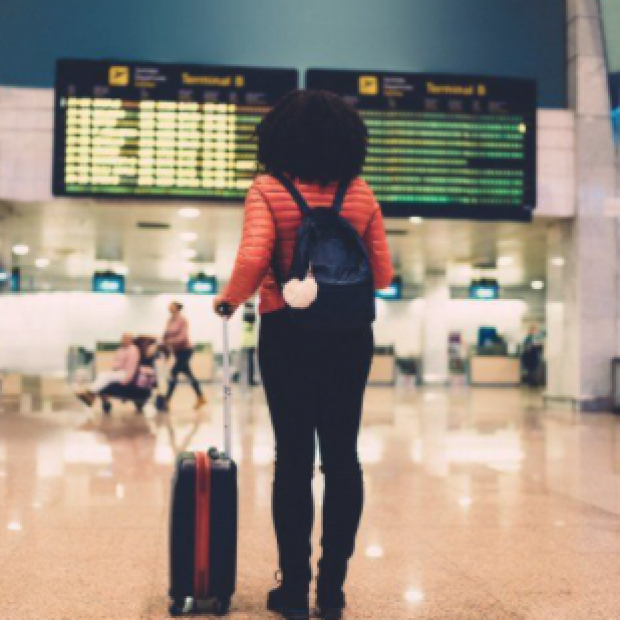 Woman with suitcase looks at airport arrivals board, image from UCSF press release