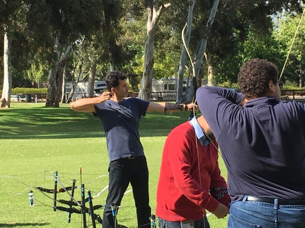 Lab member shooting a bow and arrow