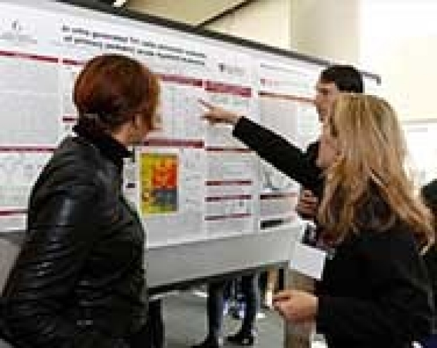 Attendees pointing at poster