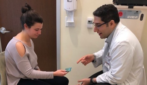 Doctor pointing at device in patient