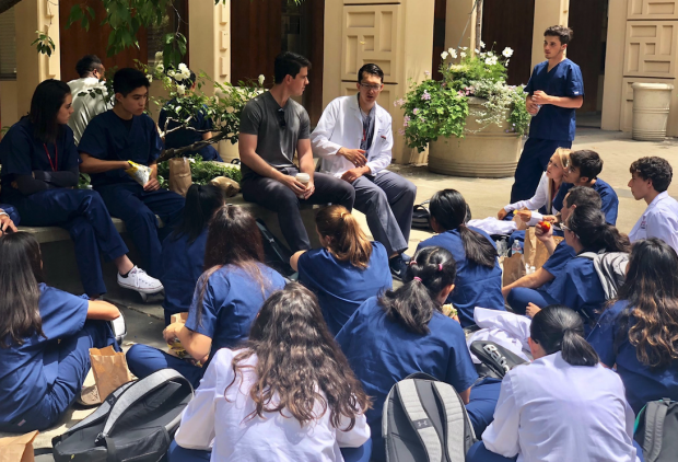 Students at lunch grouped around individual in white coat