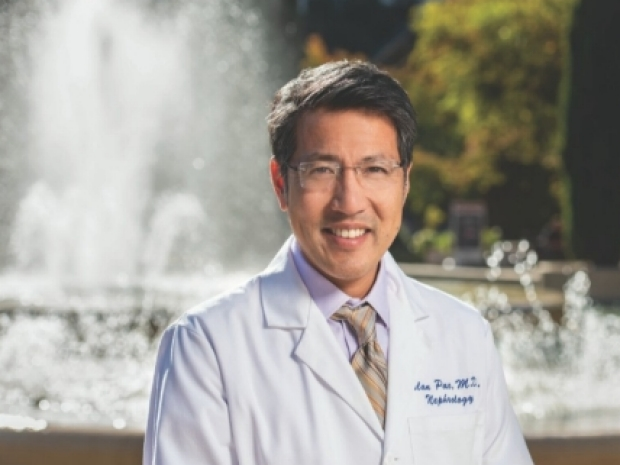 Alan Pao, MD stands in front of the Stanford Hospital fountain