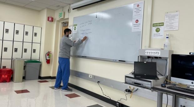 Fellow writing on white board