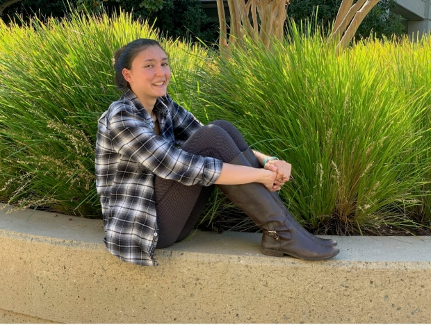 A young woman with dark hair wearing a plaid shirt and leggings, sits in front of bushes.