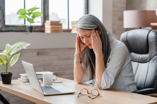 Woman at computer with glasses and migraine headache