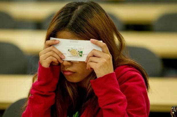 Girl looking through a Foldscope
