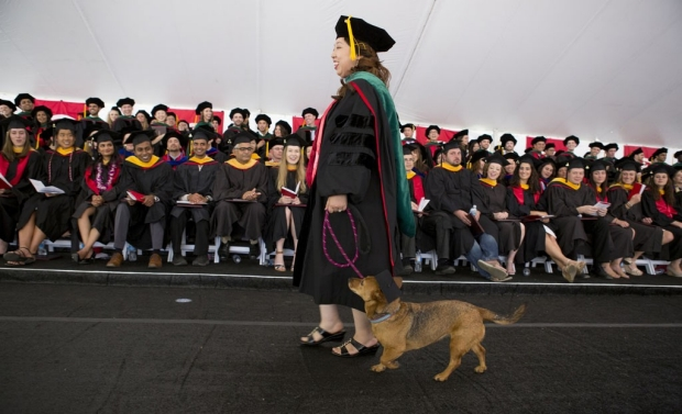 Graduate walking across stage with her dog