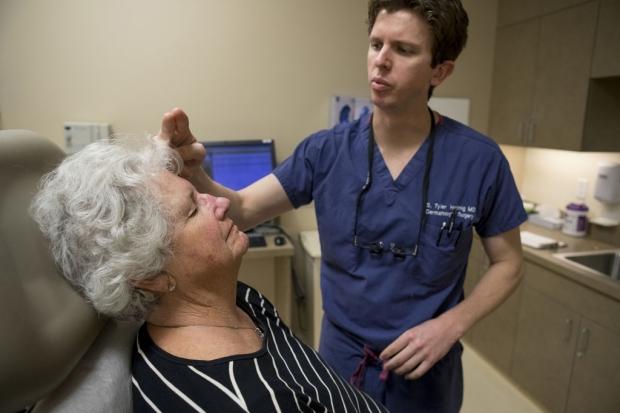 Doctor examining a woman's face