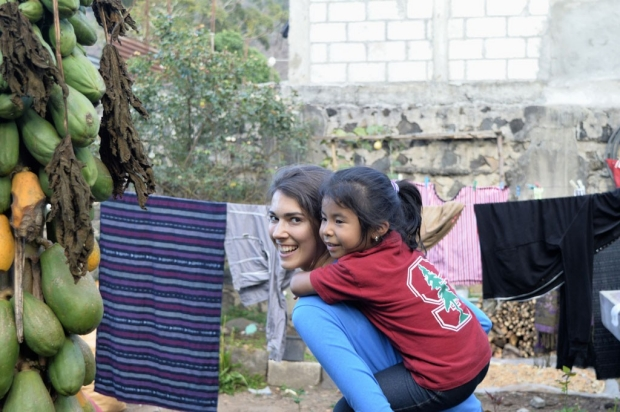 Medical student giving a piggyback ride to a Guatemalan girl