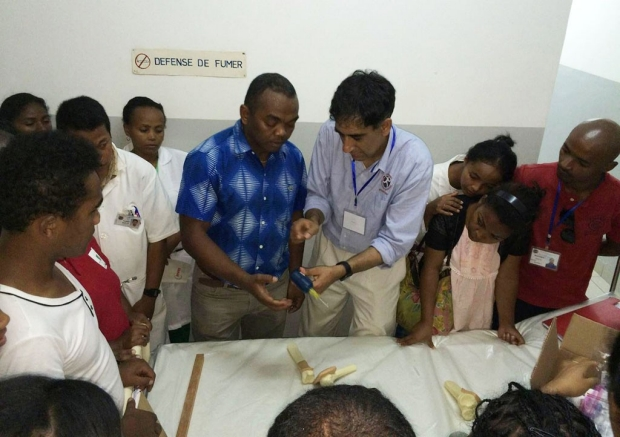 Doctor showing health-care workers how to use a special needle