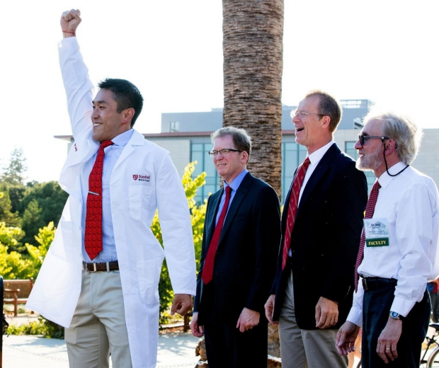 Medical student raising his arm in triumph after receiving his white coat