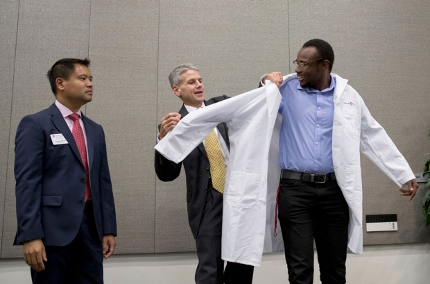 Student being helped into his new lab coat