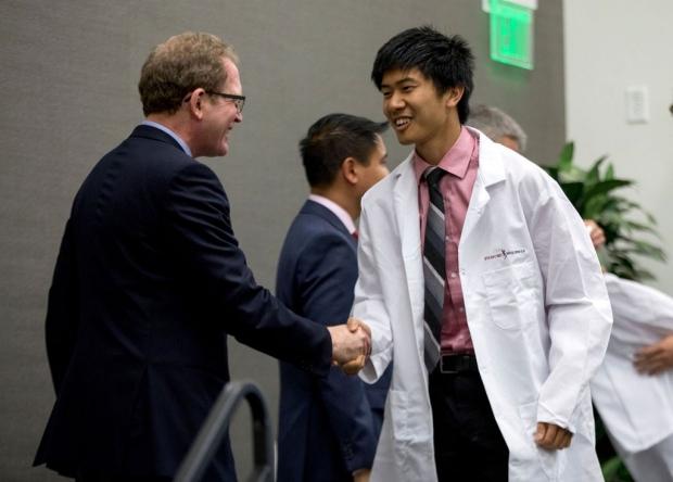 Dean congratulating a student