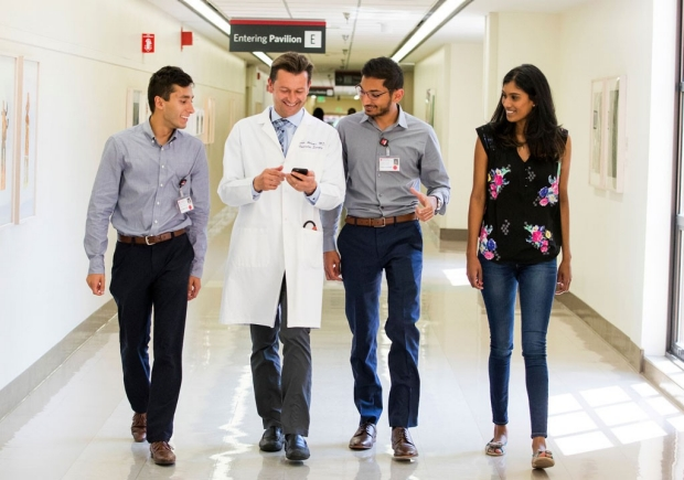 Doctor walking with students in a hallway