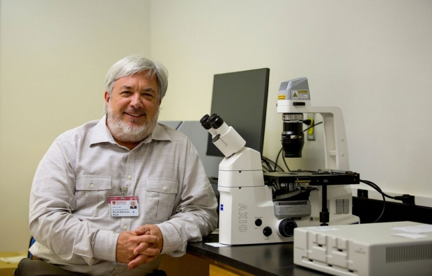 David DiGuisto sitting by a microscope