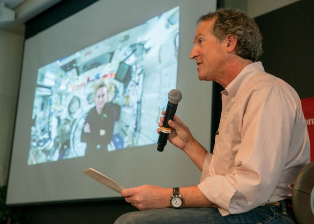 Man with a microphone talking to a woman astronaut during a video conference