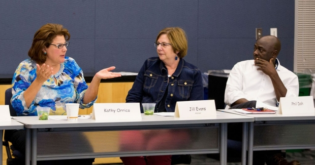Two women talking at a table while a man looks on