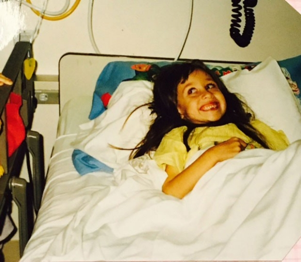 Young girl lying in a hospital bed and smiling