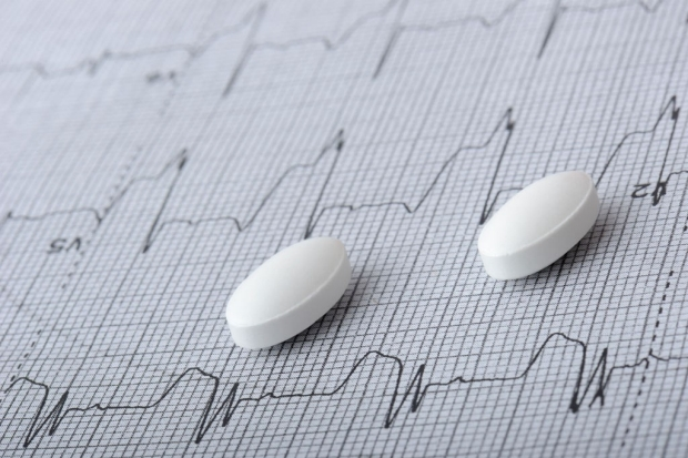 Two pills on top of a readout of a heart rate