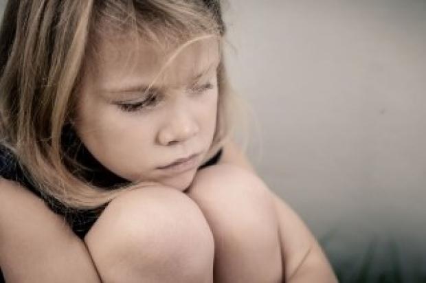 Sad girl hugging her knees
