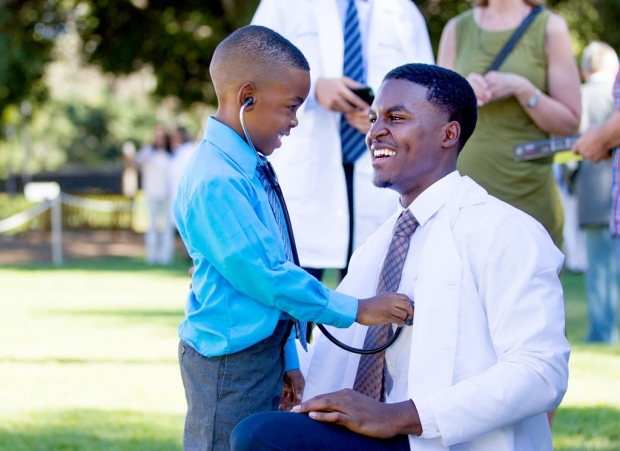 Young boy using a stethoscope to listen to the heart of a medical student