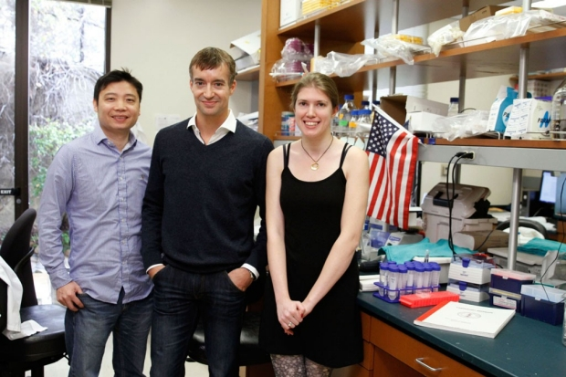 Two men and a woman standing in a research laboratory