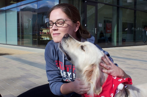 A medical student gets nuzzled by a therapy dog
