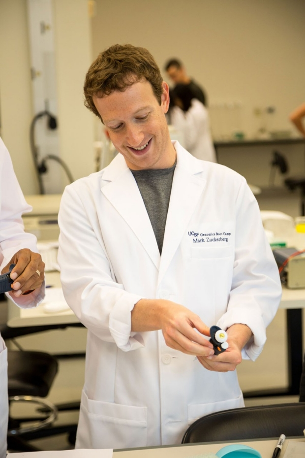 Man in a lab coat holding a test tube