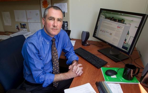 Man in a blue shirt seated at a desk near a computer screen