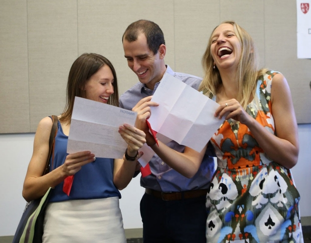 A man between two women as they all reading their Match Day letters